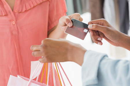 Closeup mid section of female customer receiving shopping bags and credit card from saleswoman in boutique photo