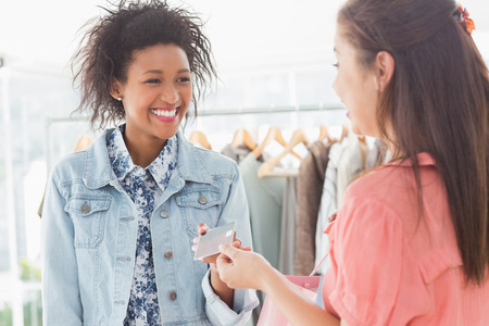 Female customer receiving credit card from saleswoman in boutique photo