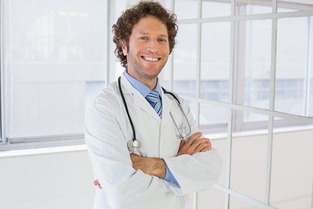 Portrait of a happy handsome male doctor standing with arms crossed in the hospital photo