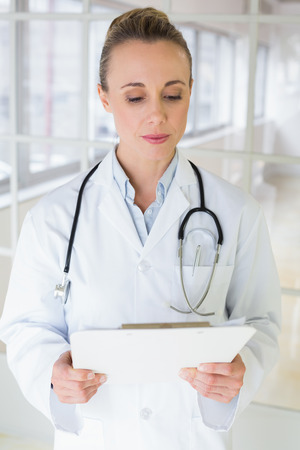 Beautiful young female doctor with clipboard standing in the hospital photo