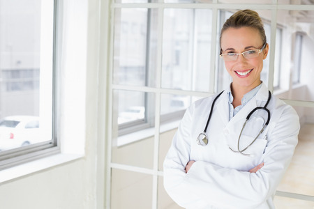 Portrait of a beautiful happy female doctor standing with arms crossed in the hospital photo