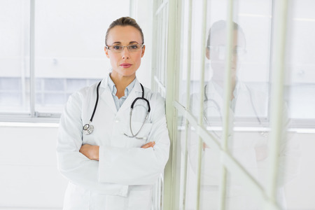 Portrait of a beautiful serious female doctor standing with arms crossed in the hospital photo