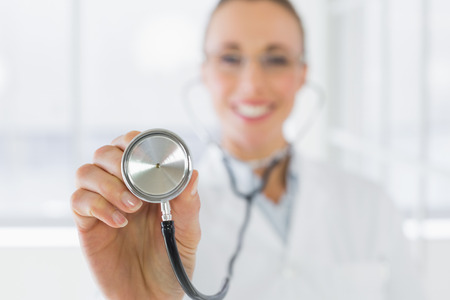 Closeup of a blurred smiling female doctor with stethoscope in a bright hospital photo