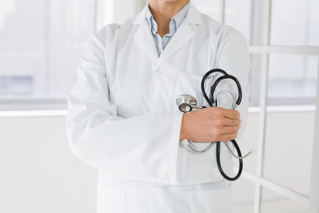 Closeup mid section of a female doctor standing with stethoscope in the hospital photo