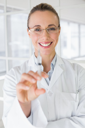 Smiling female doctor holding an injection in the bright hospital photo