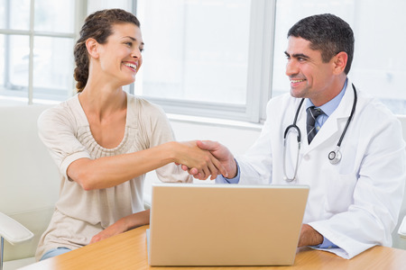 Male doctor and patient shaking hands by laptop at desk in medical office photo
