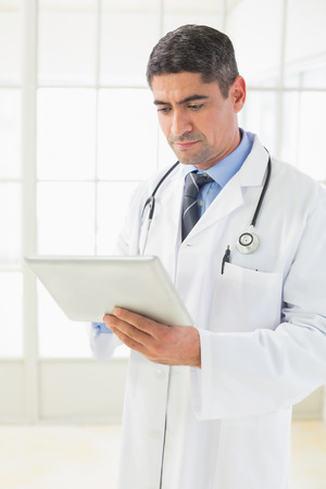 Serious male doctor using digital tablet in the hospital photo