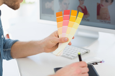 Designer working with digitizer holding colour chart at his desk in creative office photo
