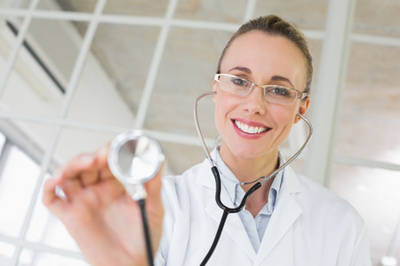 Portrait of a female doctor with stethoscope in a bright hospital photo