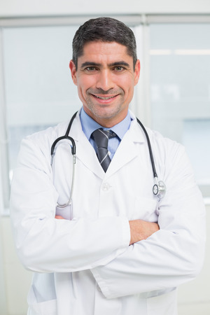 Portrait of a smiling male doctor standing with arms crossed in the hospital photo
