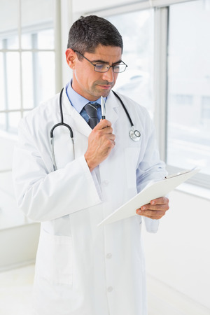 Concentrated male doctor reading reports in the hospital photo