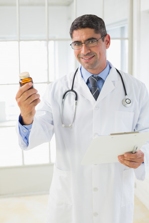 Portrait of a smiling male doctor holding a bottle of pills in the hospital photo
