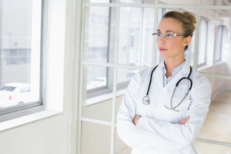Beautiful serious young female doctor standing with arms crossed in the hospital photo