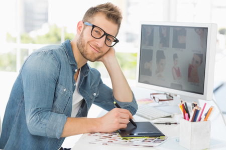 graphics tablet: Handsome editor working with graphics tablet smiling at camera in creative office Stock Photo