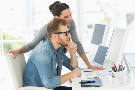 an office work: El equipo de diseñadores que buscan en la computadora en la oficina creativa