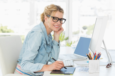 Blonde pretty designer looking at the camera using digitizer in creative office photo