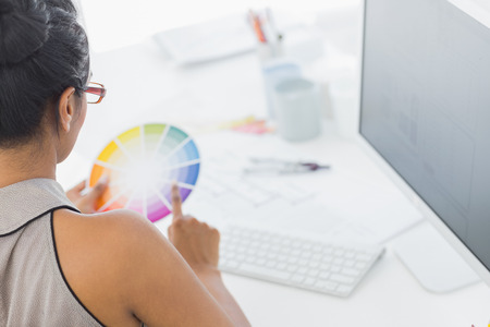 Designer working at her desk holding colour wheel in creative office photo