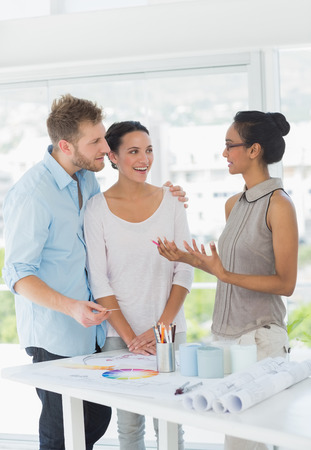 Interior designer speaking with happy clients in creative office photo