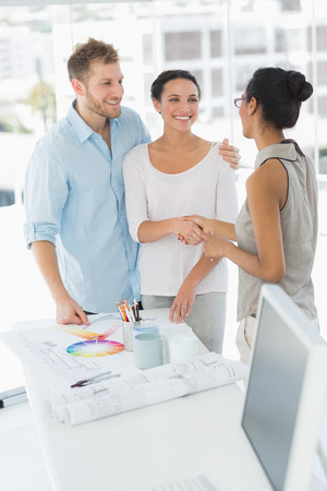 Interior designer shaking hands with smiling client in her studio Stock Photo