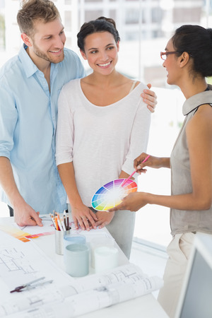 Interior designer showing colour wheel to happy clients in her studio photo