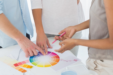 Interior designer showing colour wheel to customers in her studio photo