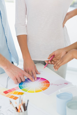 Interior designer showing colour wheel to two customers in her studio photo