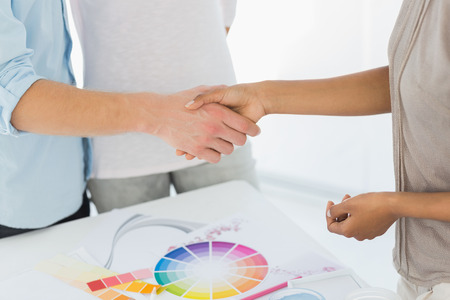 Interior designer shaking hands with customer in her studio photo