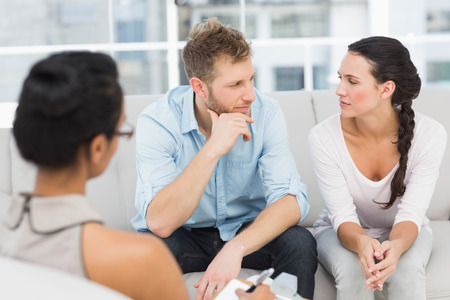 Unhappy couple at therapy session in therapists office photo