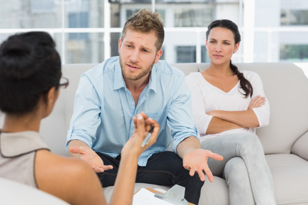 counselling: Unhappy couple at therapy session with man talking to therapist in therapists office