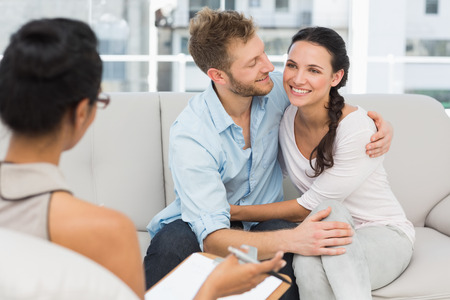 Happy couple reconciling at therapy session in therapists office photo
