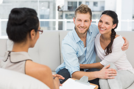 counselling: Smiling couple reconciling at therapy session in therapists office