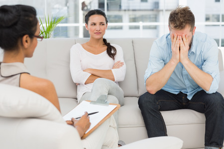 Unhappy couple sitting on sofa at therapy session in therapists office photo