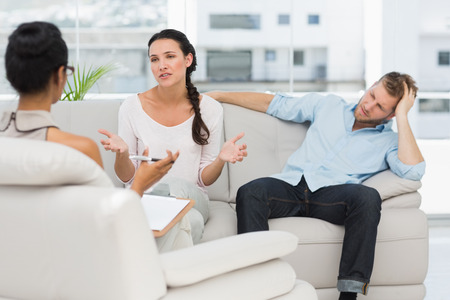 Angry couple sitting on couch talking to therapist in therapists office photo