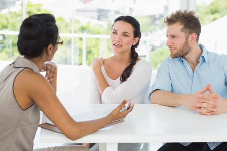 Terapeuta conversando com casal sentado na mesa no escrit