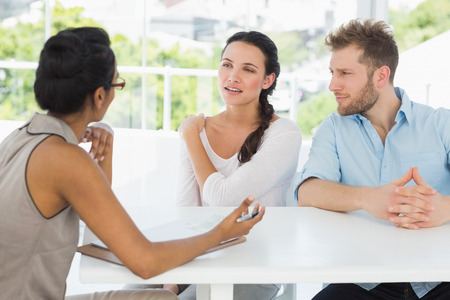 counselling: Therapist talking with couple sitting at desk in therapists office