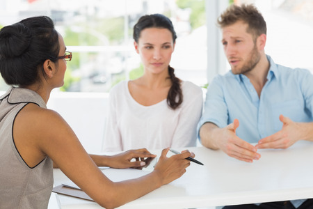 Therapist speaking with couple sitting at desk in therapists office photo