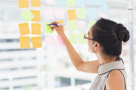 lluvia de ideas: Dise�ador sonriente escrito en notas adhesivas en la ventana de la oficina creativa