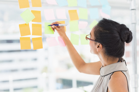 Smiling designer writing on sticky notes on window in creative office Stock Photo