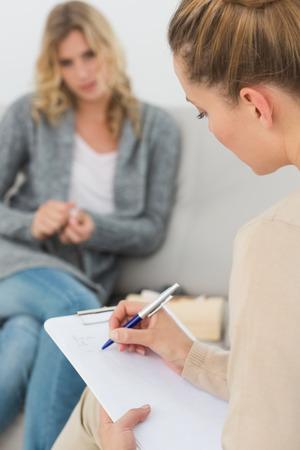 Terapeuta escribir notas en su portapapeles en la sesión de terapia