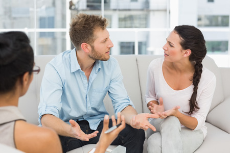 marriage counseling: Unhappy couple arguing at therapy session in therapists office