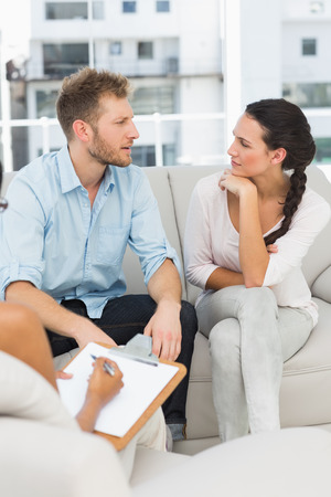Unhappy couple talking at therapy session in therapists office photo
