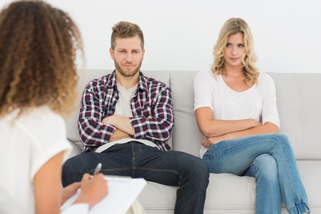 Unhappy couple not talking on the couch at therapy session photo