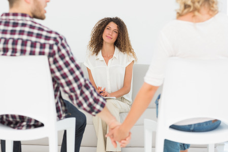 marriage counseling: Therapist smiling at reconciled couple holding hands at therapy session