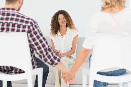 27146741: Happy therapist smiling at reconciled couple holding hands at therapy session