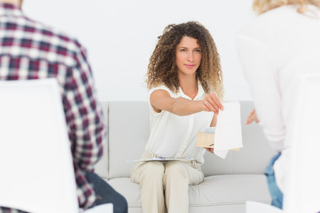 couples therapy: Therapist handing a tissue to woman at couples therapy at therapy session