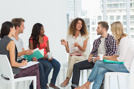 support group: Smiling therapist speaking to a rehab group at therapy session Stock Photo