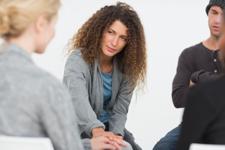 therapy group: Woman comforting another in rehab group at a therapy session