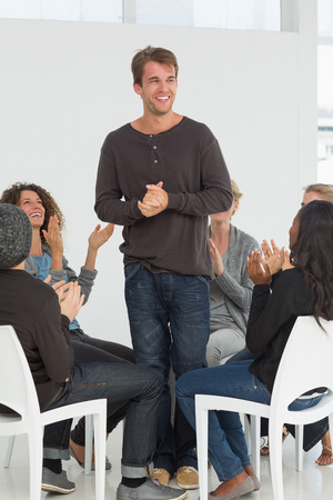 applauding: Rehab group applauding happy man standing up at therapy session