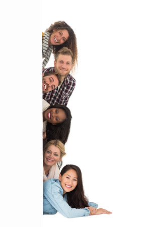 Happy group of young friends peeking from behind a wall on white background photo