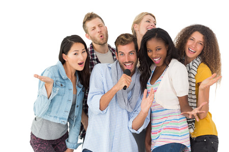 Happy group of friends having fun doing karaoke on white background photo